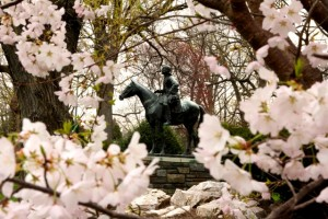 Statue of John Wesley surrounded by blossoms.
