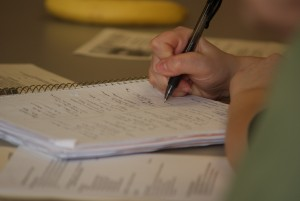 Image: Student writing in a spiral notebook